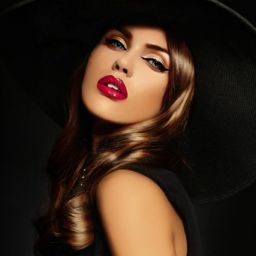 High fashion look.glamor closeup portrait of beautiful sexy stylish Caucasian young woman model with bright makeup, with red lips, with perfect clean skin in big black hat